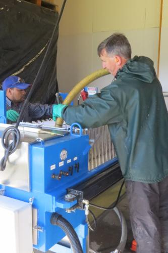 Bill fills the bags of the pressing machine with pommace